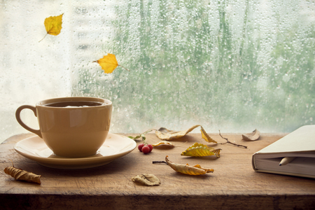 Photo pour Cup of autumn tea (coffee, chocolate) with note book and yellow dry leaves near a window, copy space. Hot drink for autumn cold rainy days. Hygge concept, autumn mood. - image libre de droit