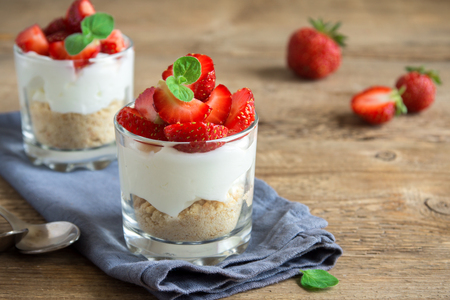 Photo pour Strawberry trifle mini dessert in glasses with fresh strawberries and cream cheese  on wooden background. Healthy homemade potrion dessert. - image libre de droit