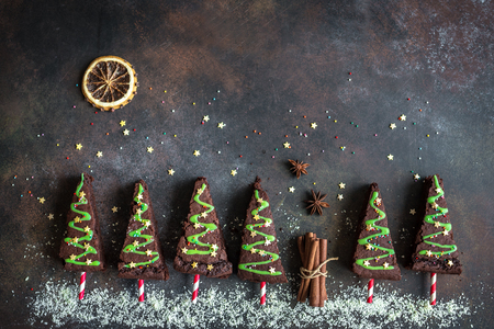 Foto de Chocolate Brownies in shape of Christmas Trees with green icing and festive sprinkles, top view, copy space. Sweet Christmas or winter holidays pastry food concept. - Imagen libre de derechos