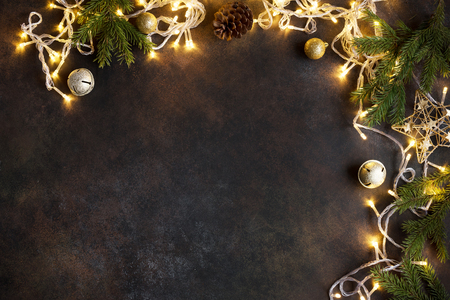 Photo for Christmas frame with lights, golden balls, fir branches on dark background with copy space. Christmas festive garland and decor. - Royalty Free Image