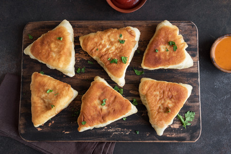 Photo for Deep fried meat pies, samsa, samosas, echpochmak - traditional meat stuffed pies or vegetarian pies on rustic background, top view. - Royalty Free Image