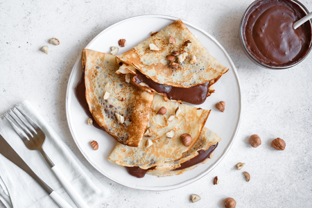 Photo pour Crepes with chocolate spread and hazelnuts. Homemade thin crepes for breakfast or dessert on white background, copy space. - image libre de droit