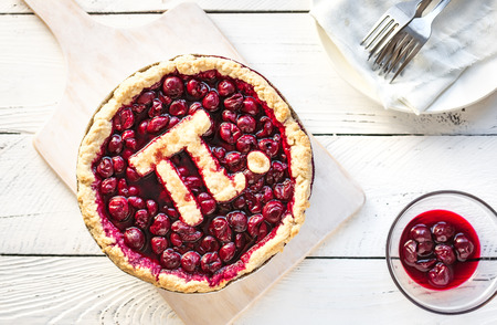 Pi Day Cherry Pie - Homemade Traditional Cherry Pie with Pi sign for March 14th holiday, on white wooden background, top view, copy space.