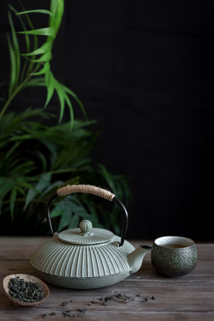 Photo for Teapot and Teacups on black background, copy space. Traditional Asian arrangement  for Tea ceremony -  iron teapot and ceramic teacups with tea. - Royalty Free Image