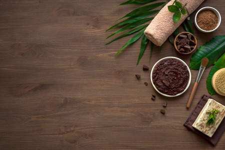 Foto per Chocolate Spa composition with plants and flowers, flat lay, copy space. Natural spa chocolate products and organic treatment concept on dark wooden background. - Immagine Royalty Free
