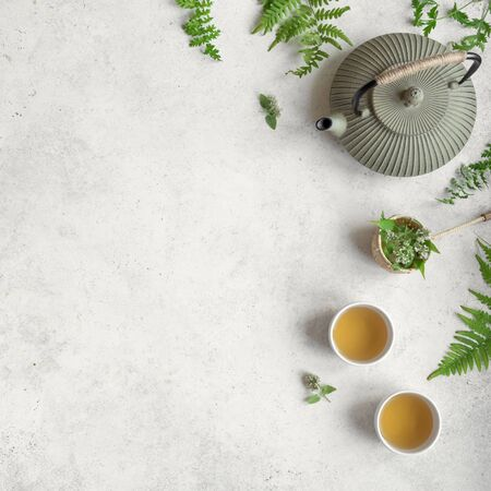 Photo pour Herbal or Green Tea on white background, top view, copy space. Teapot and teacups with wild plant leaves, natural herbal tea composition. - image libre de droit