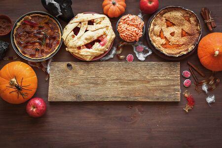 Photo pour Halloween Pies - pumpkin, mummy, brain, worms. Festive Halloween homemade pastries and desserts assortment and autumn decor, top view, copy space. - image libre de droit