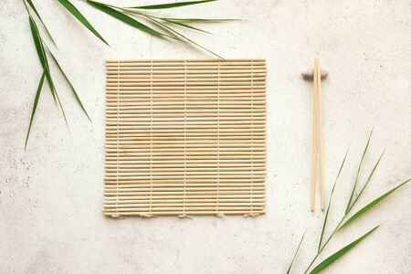 Photo pour Asian food background - chopsticks, bamboo mat with bamboo leaves on light background. Asian menu design, chinese japanese cuisine concept. - image libre de droit