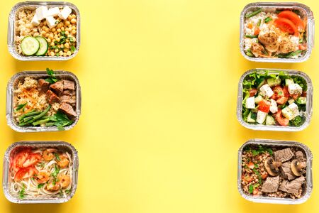 Foto de Healthy food delivery. Take away of organic daily meal on yellow, copy space. Clean eating concept, healthy food, fitness nutrition take away in foil boxes, top view. - Imagen libre de derechos