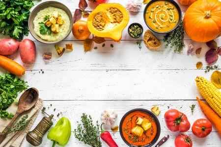 Foto de Autumn soups. Set of various seasonal vegetable soups and organic ingredients on white background, top view, copy space. Homemade colourful vegan soups. - Imagen libre de derechos