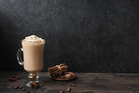 Photo for Irish Coffee with whipped cream, spices and coffee beans on black wooden background, copy space. - Royalty Free Image
