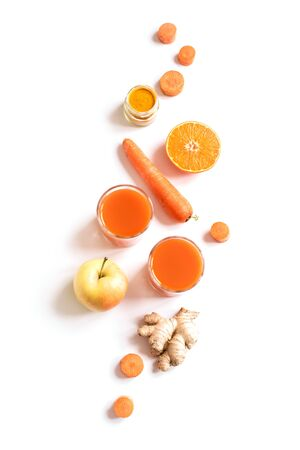 Photo pour Detox cleanse drink, orange fruit and vegetable smoothie ingredients. Natural, organic healthy juice in glasses for weight loss diet or fasting day. Carrot, apple, ginger, turmeric powder and orange mix isolated on white. - image libre de droit