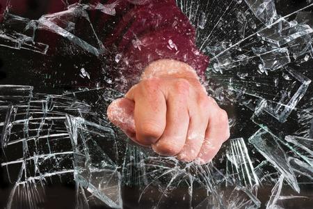 Photo pour Hand through broken glass window. - image libre de droit