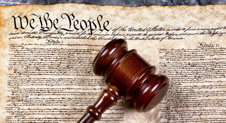 Wooden gavel on top of American Bill of Rights document, We the People.