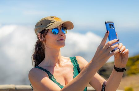 Photo pour Woman in the cap and sunglasses taking selfie photo on the cloud background - image libre de droit