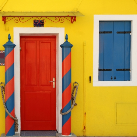 traditional colorful doorway to the home in Burano village, borgo on venetian lagoon famous for vivid painted houses, Venice