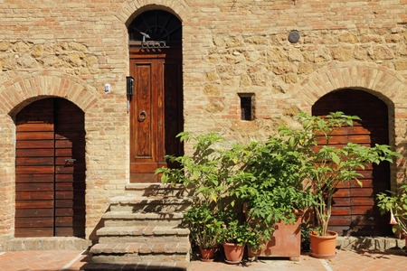 picturesque old wall with doors in tuscan village Pienza Italy