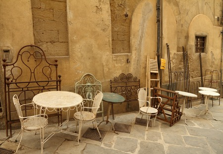 assortment of old fashion furniture objects displayed on street  during  famous Antiquity  Market in tuscan town Arezzo , Italy, Europe