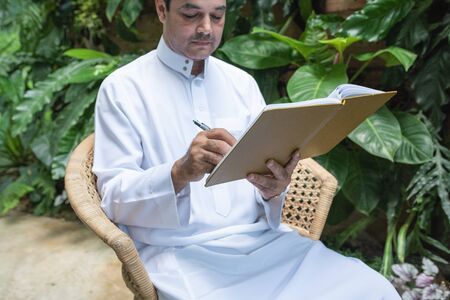 Photo pour Saudi muslim man dress hijab sitting and writing on textbook, freelance business concept. - image libre de droit