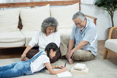 Photo pour Happy young asian granddaughter reading and writing book with grandfather and grandmother looking beside on floor in living room at home,Retirement domestic life concept. - image libre de droit