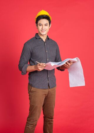 Photo pour Young handsome asian man in casual dress with yellow hardhat hand holding paperwork blueprint  in architect and engineer worker isolated in red background in studio. - image libre de droit