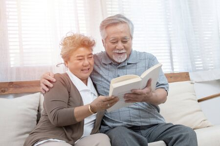 Photo pour Elderly senior asian couple sitting on sofa reading book together at home.Retirement grandmother and grandfather spend time together at house. - image libre de droit
