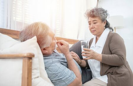 Foto für Asian Senior woman look after give glass of water to elder man taking medicines and drinking water while lie on couch at home, health and medicine concept with copy space. - Lizenzfreies Bild