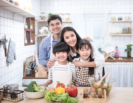 Photo pour Happy young family have leisure time in kitchen,Father help mother cooking,daughter and son eat yam and bread. - image libre de droit