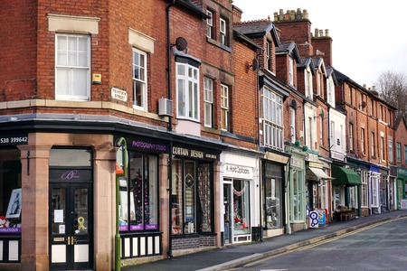 Photo for LEEK, UK - DECEMBER 31 2015: A row of small, independent shops occupies the ground floor of historic red brick terraced houses along Fountain Street in Leek, a historic market town in the Staffordshire Moorlands, England. - Royalty Free Image