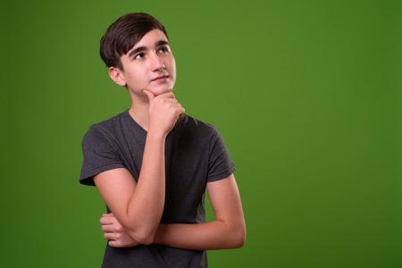 Photo pour Young handsome Iranian teenage boy against green background - image libre de droit