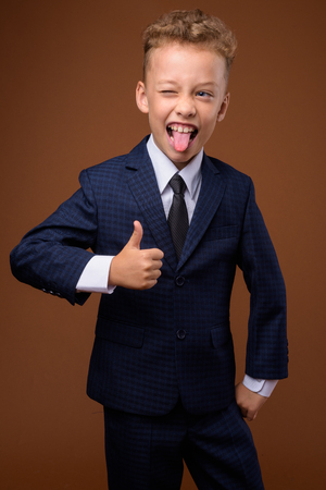 Photo pour Young boy as businessman against brown background - image libre de droit