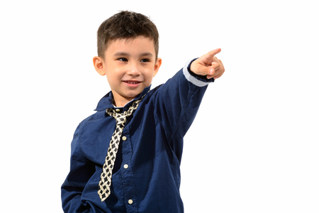 Studio shot of cute happy boy smiling and pointing finger in the