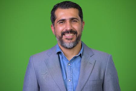 Photo pour Handsome Persian bearded businessman against green background - image libre de droit