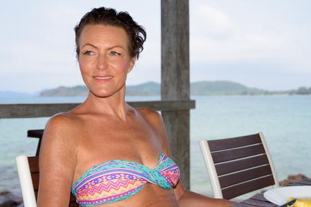 Photo pour Mature beautiful tourist woman at the beach resort - image libre de droit