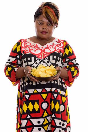 Studio shot of fat black African woman holding bowl of potato ch