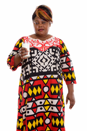 Studio shot of fat black African woman standing while holding gl