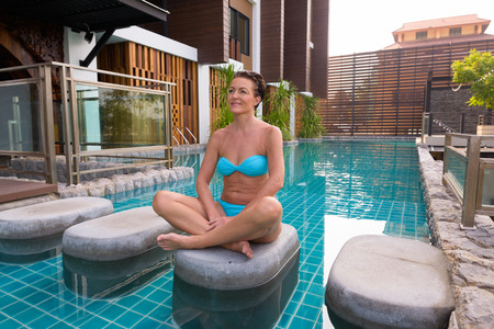 Foto de Mature tourist woman doing yoga and meditation next to swimming pool - Imagen libre de derechos