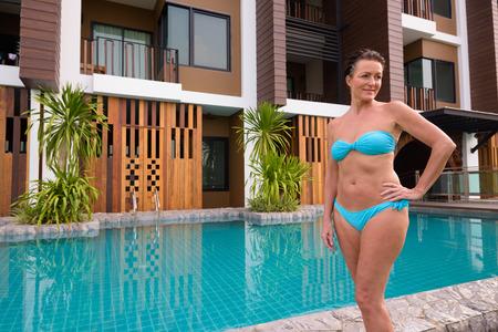 Foto de Mature beautiful Scandinavian tourist woman in bikini standing next to swimming pool - Imagen libre de derechos