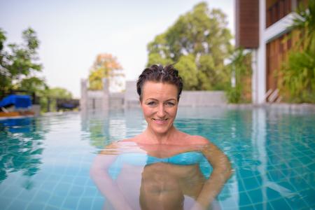 Foto de Mature beautiful Scandinavian tourist woman in swimming pool - Imagen libre de derechos