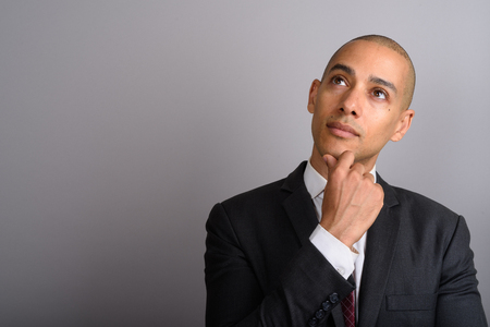 Photo pour Handsome bald businessman thinking and looking up - image libre de droit