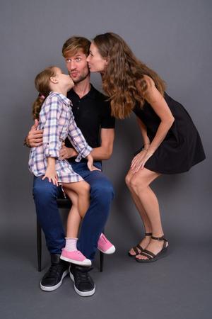 Photo pour Young happy family bonding together against gray background - image libre de droit