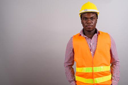 Photo pour Young African man construction worker against white background - image libre de droit