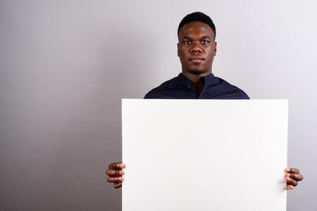 Foto de Young African businessman holding white board against white back - Imagen libre de derechos
