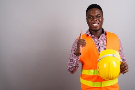 Foto de Young African man construction worker against white background - Imagen libre de derechos