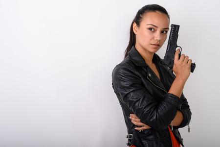 Foto de Studio shot of young Asian woman thinking while holding handgun - Imagen libre de derechos