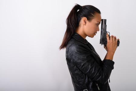 Foto de Profile view of young Asian woman holding handgun against white - Imagen libre de derechos
