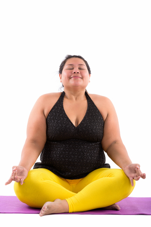 Studio shot of young fat Asian woman meditating with eyes closed