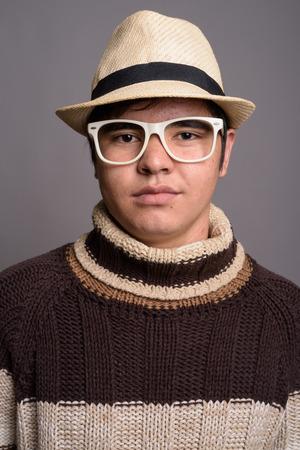 Stylish young Asian teenage boy wearing warm clothing against gr