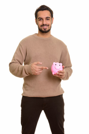 Photo for Young happy Indian man holding piggy bank and pointing finger - Royalty Free Image