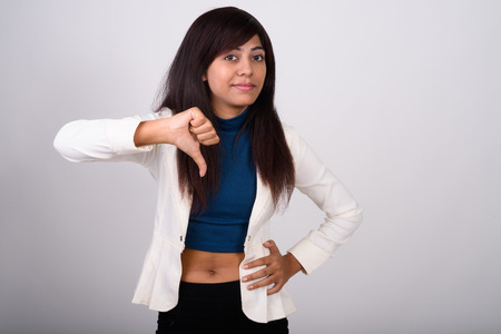 Photo for Studio shot of young Persian businesswoman giving thumb down aga - Royalty Free Image